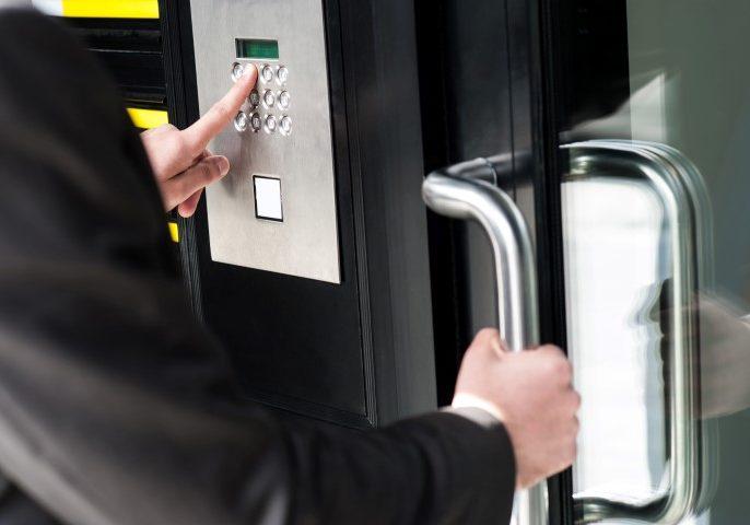 Businessman entering safe code to unlock the door.